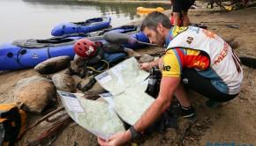 GODZone competitor Noel O'Leary looking at maps beside Lake Hauroko